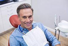 A middle-aged man smiling during a follow-up visit after having a tooth removed