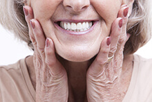 An older woman holding her face between her hands and smiling to show off her new dentures