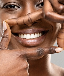 Woman framing healthy, white, straight teeth with fingers
