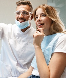 Patient and dentist smiling at monitor during consultation