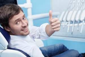 Man smiling in dental chair happy to visit the dentist ft. collins residents love
