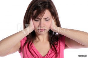 woman covering ears and frowning