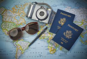 sunglasses camera passports pen map