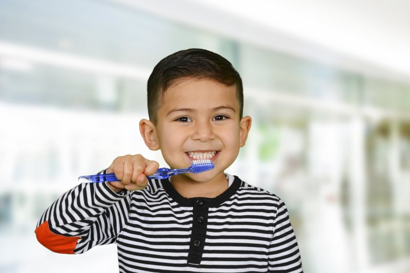 boy smiling brushing his teeth