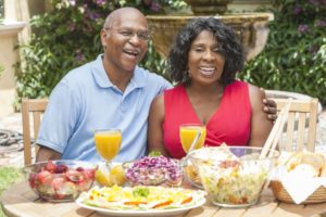 couple with dental implants sitting outside at a table with food
