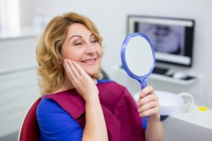 woman happy with dental implants after tooth extraction