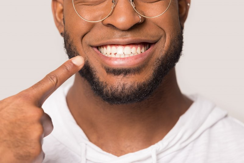 young man smiling and pointing to teeth